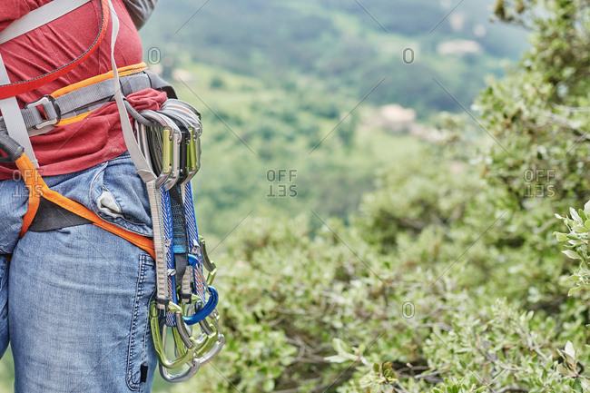 Unrecognizable crop male climber wearing safety equipment with carabiners climbing on background of green forest