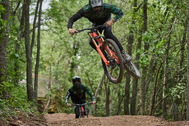 Male cyclists in protective helmets and costumes performing dangerous stunts on bikes for downhill on trail in forest