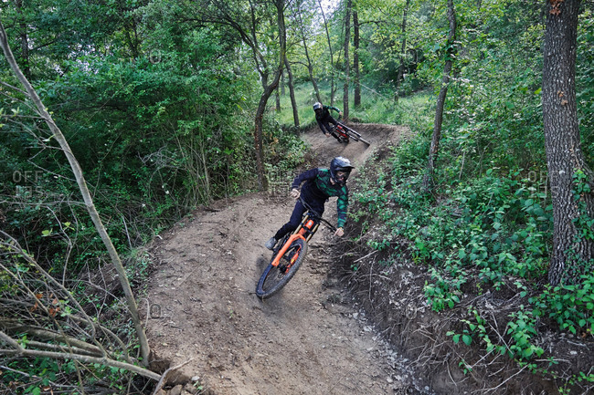 Male cyclist on bike for downhill riding along sandy path and performing extreme trick in woods