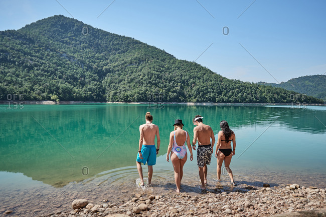 Back view of company of tourists in swimwear walking together in calm lake on sunny day during vacation in highland area