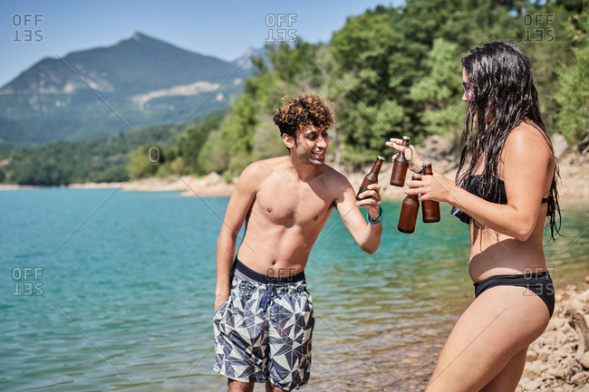 Side view of group of friendly people in swimwear relaxing on beach near lake in mountains and clinking bottles of beer while enjoying summer holiday