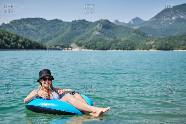 Content female with bottle of beer floating in inflatable ring on surface of calm water of pond while enjoying sunny day in summer and looking at camera