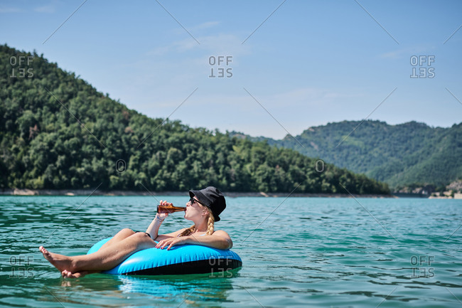Content female with bottle of beer floating in inflatable ring on surface of calm water of pond while enjoying sunny day in summer and looking away