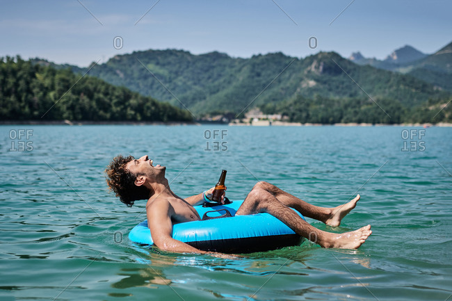 Content male with bottle of beer floating in inflatable ring on surface of calm water of pond while enjoying sunny day in summer and smiling