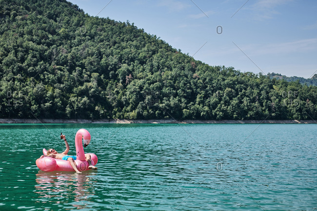 Relaxed male with bottle of refreshing drink lying on inflatable ring in shape of flamingo and floating on lake during summer vacation