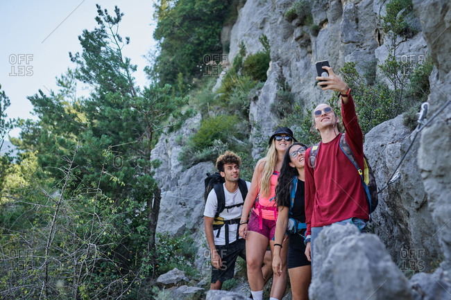 Group of friendly tourists with backpacks standing in highland area and taking photo on selfie camera during vacation