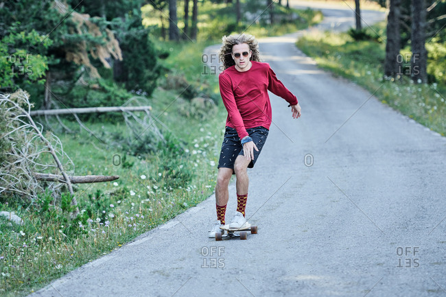 Concentrated male hipster in fancy clothes and with long hair riding skateboard along road in park in summer