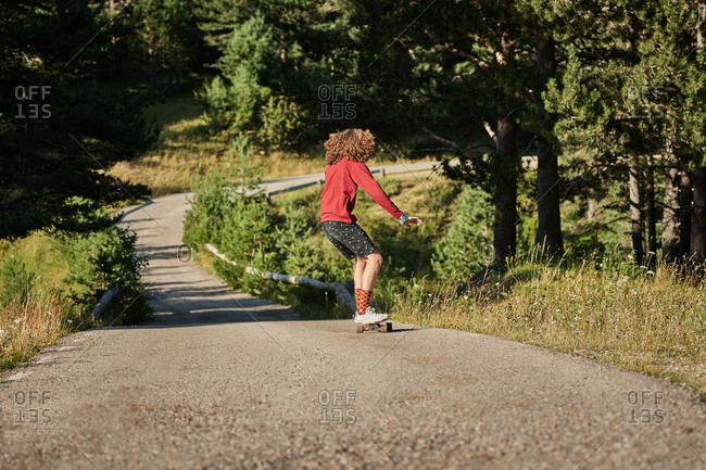 Back view of male hipster in fancy clothes and with long hair riding skateboard along road in park in summer