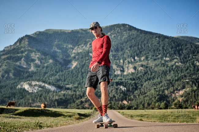 Concentrated male hipster in fancy clothes and with cap riding skateboard along road in park in summer