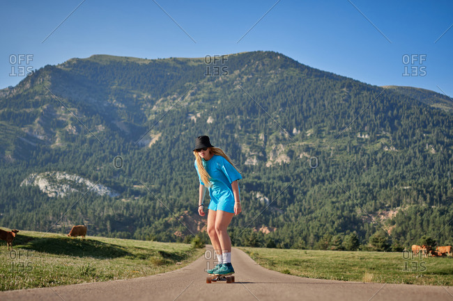 Full body of focused female skater riding skateboard along rural road while enjoying weekend in summer on background of mountains