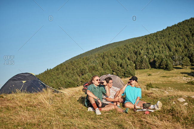 Company of friends sitting near camping tents while drinking refreshing beverages and resting after hiking on sunny day