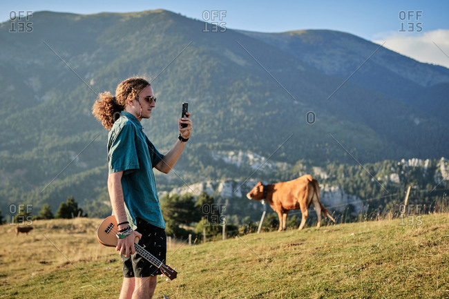 Side view of male hipster with long hair and ukulele taking picture of amazing scenery in mountains while standing on hill and relaxing during summer weekend