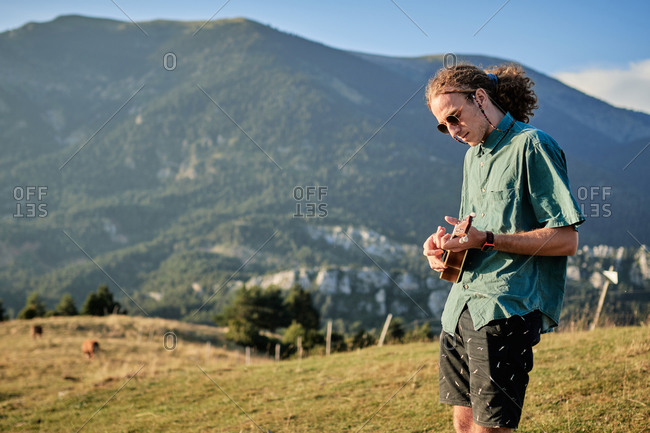 Side view of male hipster with long wavy hair playing melody on ukulele while standing on background of wonderful highland scenery in summer