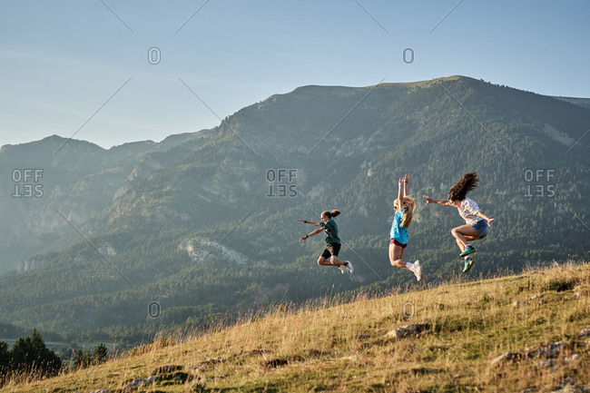 Company of delighted friends jumping on hill in mountains while enjoying freedom during summer vacation