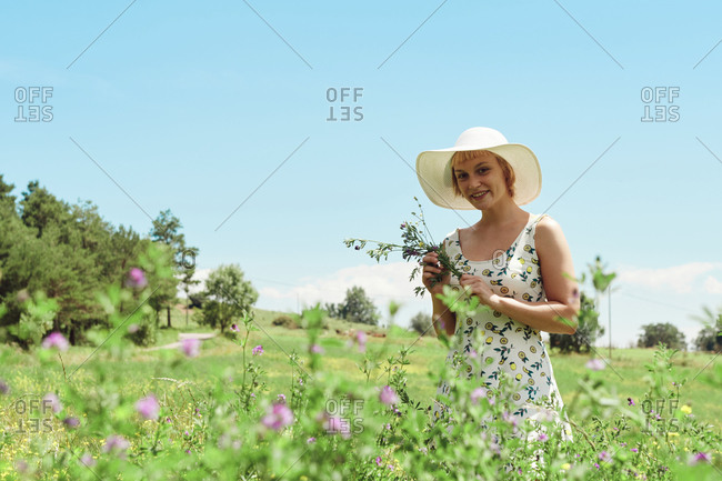 Content female in summer dress and hat standing with bouquet of wildflowers in blossoming meadow and looking at camera