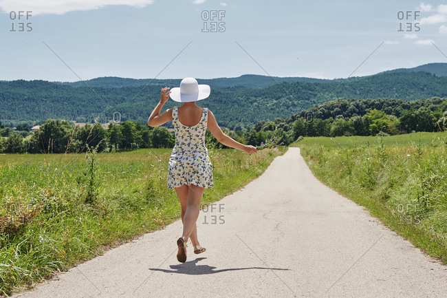 Back view of female wearing dress and sunhat walking with bunch of flowers along road on background of mountains and looking away