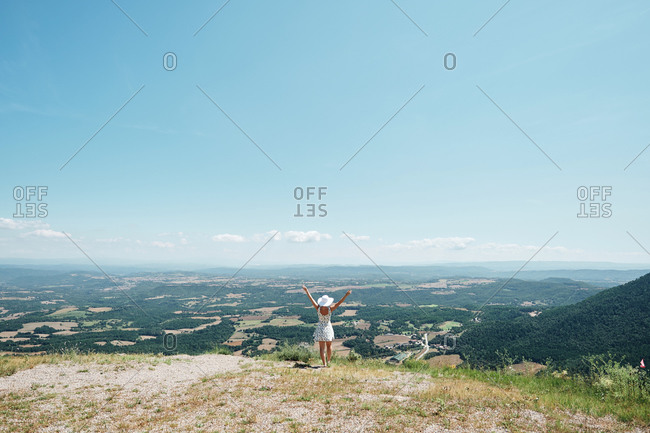 Back view of female in dress standing on hill with raised arms and enjoying freedom during vacation