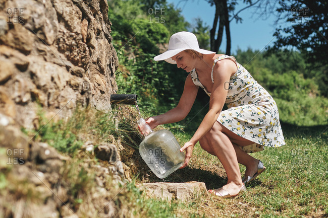 Side view of female in dress and sunhat filling plastic bottle with fresh water from natural spring in rock in sunny day