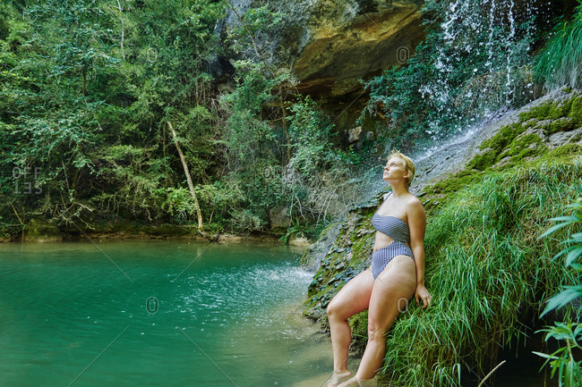 Side view of serene female in bikini leaning on rock and enjoying view of amazing waterfall in forest