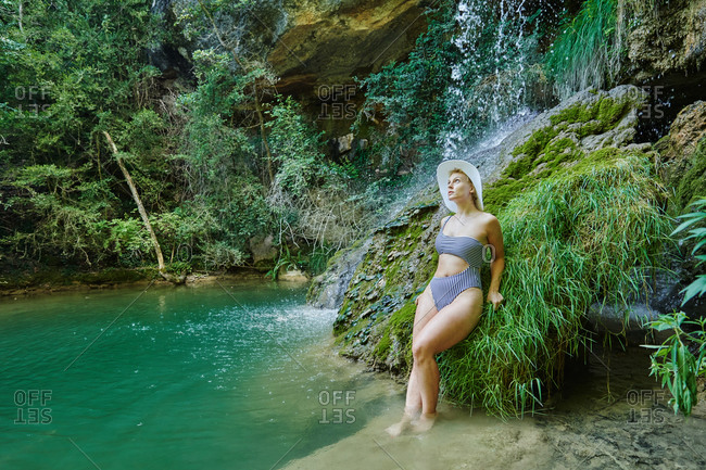 Serene female in bikini leaning on rock and enjoying view of amazing waterfall in forest