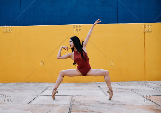 Flexible female ballet dancer performing in city near vibrant building while balancing on tiptoes in pointe shoes
