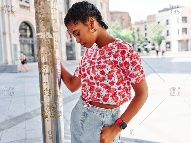 Confident young African American female in colorful shirt and jeans with wristwatch leaning on metal post and looking away while standing on city square in summer day