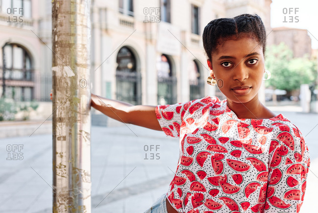 Confident young African American female in colorful shirt and jeans with wristwatch leaning on metal post and looking at camera while standing on city square in summer day