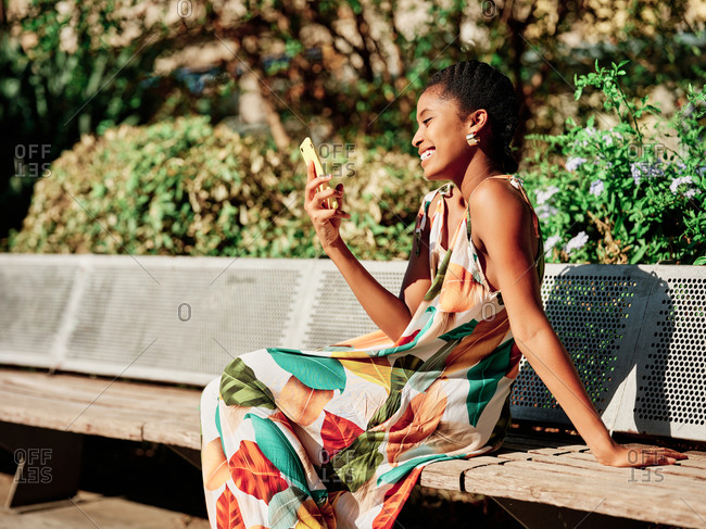Delighted young African American female in stylish colorful outfit sitting on bench and discussing news with friend during phone call while spending sunny summer day in park