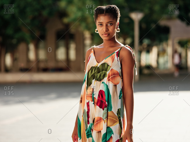 Delighted young African American female in stylish colorful outfit spending sunny summer day in park