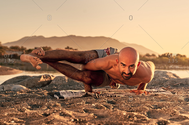 Shirtless flexible male balancing on arms in Eight Angle pose while practicing yoga and looking at camera on background of mountains in summer