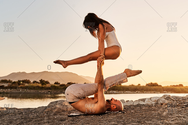 Side view of slim man and woman practicing acro yoga together in Tittibhasana while leaning on each other