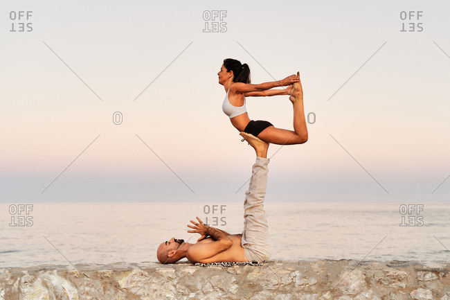 Side view of strong man lifting woman balancing in Locust pose on background of seascape during sunset while doing acroyoga