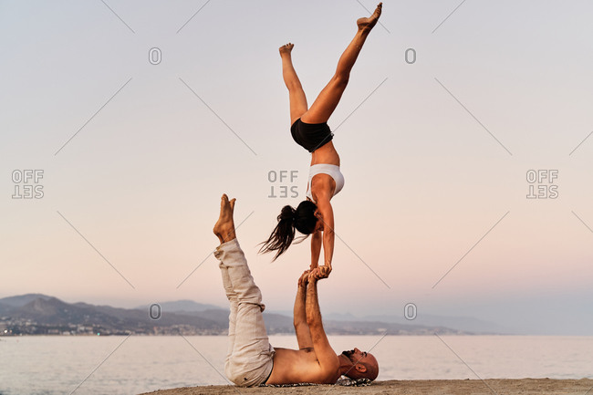 Side view of slim female in Handstand balancing on hands of strong man on background of seascape during sunset while practicing yoga together