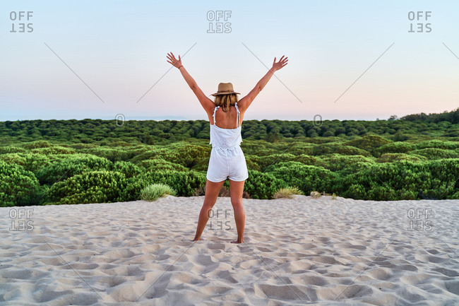 Back view of female in summer outfit standing on beach and enjoying vacation with raised arms