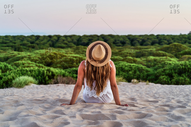 Back view of calm female sitting on beach and admiring wonderful natural landscape during sunset