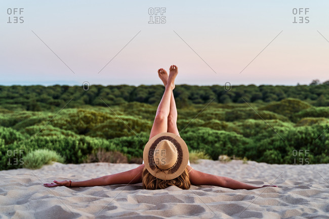 Anonymous female in straw hat relaxing on sandy shore with raised and crossed legs during sunset in summer