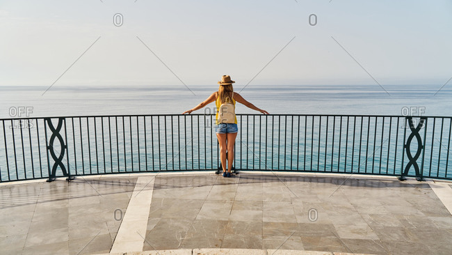 Back view of unrecognizable woman in casual clothes and hat leaning on railing and enjoying freedom while standing on terrace of Balcon de Europa in Nerja, Spain