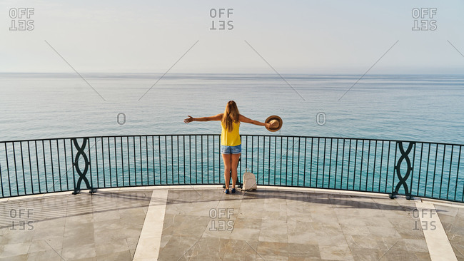 Back view of unrecognizable woman in casual clothes and hat outstretching arms enjoying freedom while standing on terrace of Balcon de Europa in Nerja, Spain