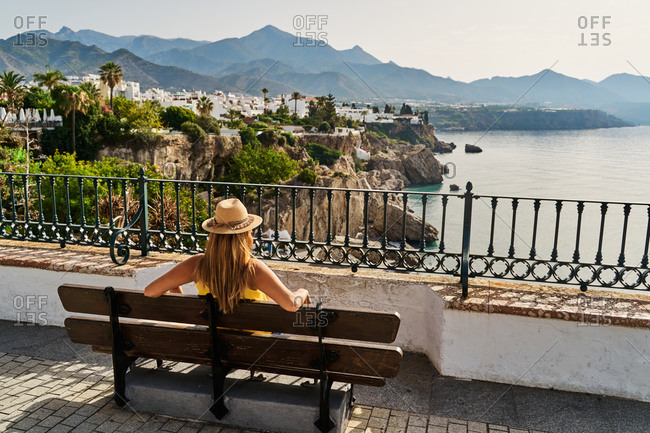 Back view of unrecognizable female in hat sitting on bench and resting on sea embankment on summer day in Nerja, Spain