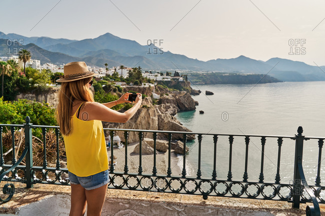 Back view of female tourist in casual clothes and hat taking photos of sea while resting on embankment on sunny day in Nerja, Spain