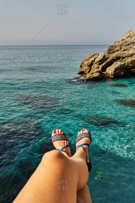 Anonymous female in stylish sandals sitting on cliff and relaxing near blue sea on summer day in  Nerja, Spain