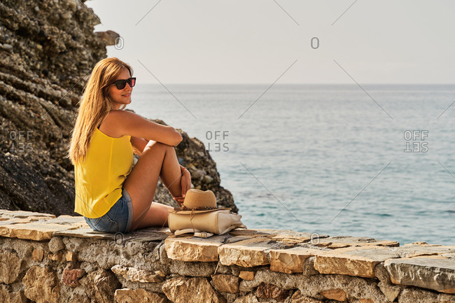 Side view of slim young woman sitting on stone barrier near sea and looking away on sunny day in Nerja, Spain