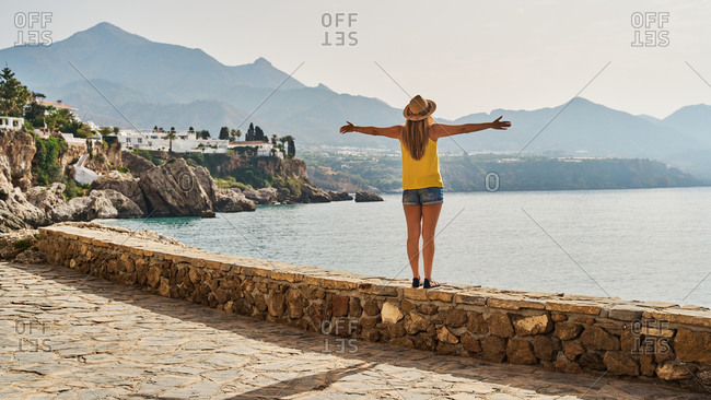 Back view of slim young woman standing on stone barrier near sea and looking away on sunny day in Nerja, Spain