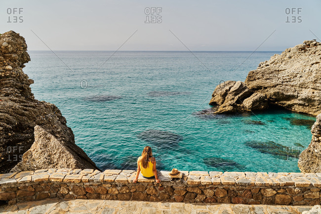Back view of slim young woman sitting on stone barrier near sea and looking away on sunny day in Nerja, Spain