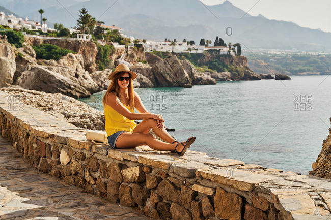 Side view of slim young woman sitting on stone barrier near sea and looking at camera on sunny day in Nerja, Spain
