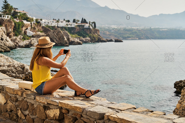 Unrecognizable woman sitting on stone border and taking photo of sea while resting on embankment on sunny day in Nerja, Spain