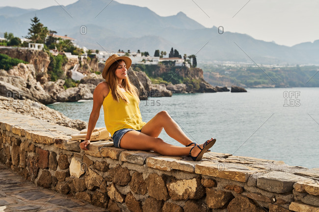 Side view of slim young woman sitting on stone barrier near sea and closed eyes on sunny day in Nerja, Spain