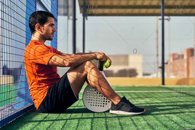 Side view of sportive ethnic male in activewear sitting on sports ground with ball and racket for paddle tennis