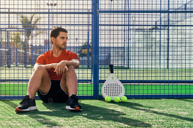 Sportive ethnic male in activewear sitting on sports ground with ball and racket for paddle tennis