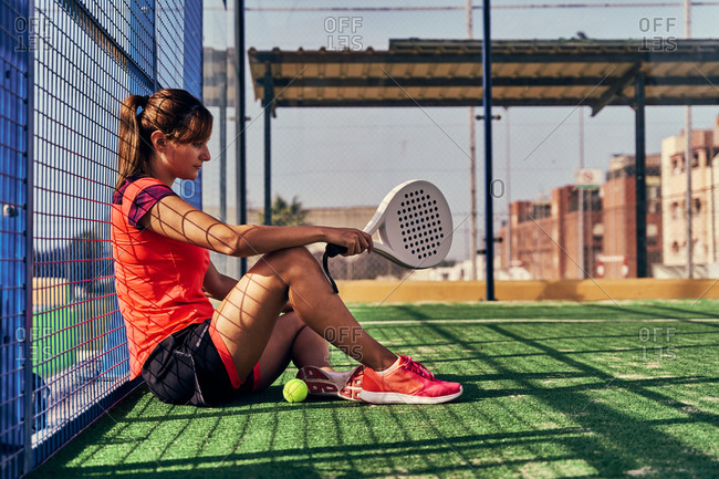 Side view of female player sitting with racket and ball on sports ground for paddle tennis